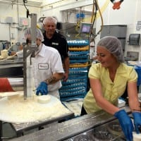 On a tour of W&W Dairy in Monroe host Mariah Haberman tries her hand at packaging Queso Fresco.